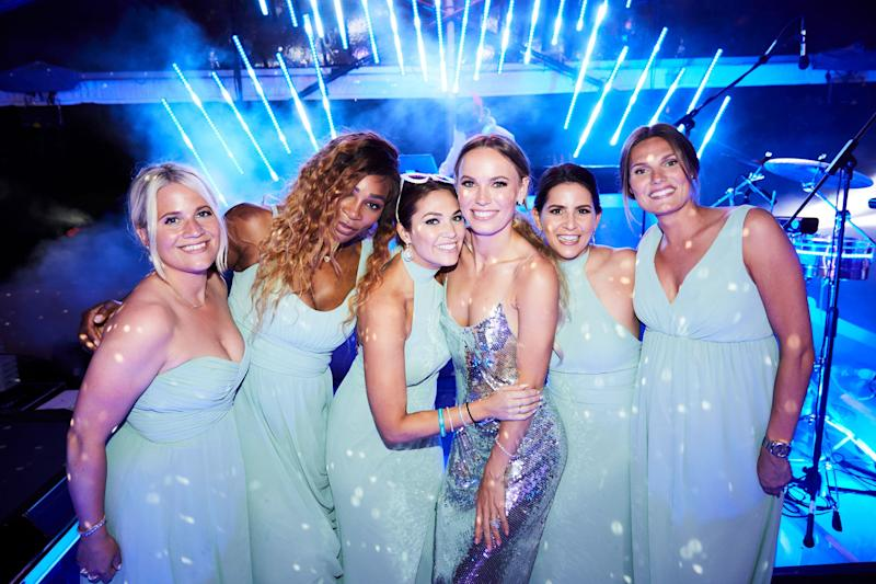 Caroline poses on stage with her bridesmaids in her final outfit of the evening—a sparkly Stella McCartney sequin dress with spaghetti straps, which she complemented with custom Adidas sneakers.