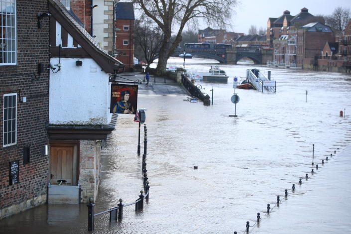 A view of a flooded street after the River Ouse burst its banks in the aftermath of Storm Ciara, in York, England, Monday, Feb. 10, 2020. Storm Ciara battered the U.K. and northern Europe with hurricane-force winds and heavy rains Sunday, halting flights and trains and producing heaving seas that closed down ports. Soccer games, farmers' markets and cultural events were canceled as authorities urged millions of people to stay indoors, away from falling tree branches.(Danny Lawson/PA via AP)