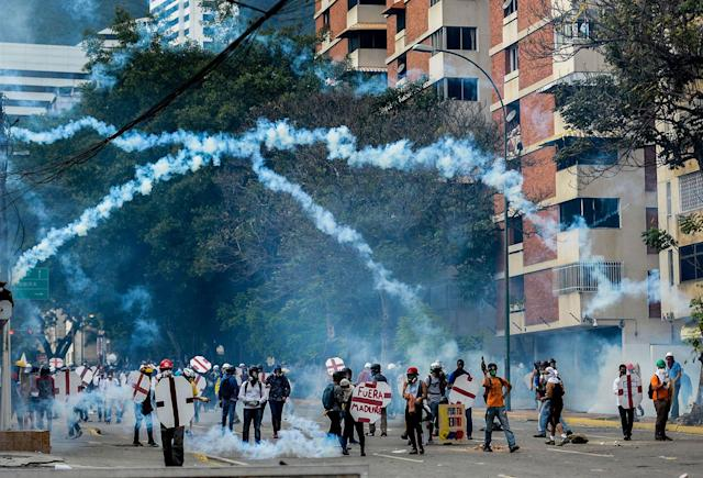 <p>Opposition demonstrators and riot police clash during a protest against Venezuelan President Nicolas Maduro, in Caracas on May 3, 2017. (Photo: FEDERICO PARRA/AFP/Getty Images) </p>