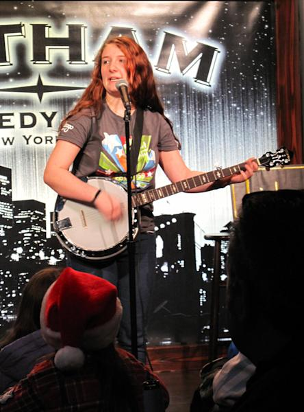 """In this Dec. 16, 2012 photo, teenage comedian Val Bodurtha plays banjo and sings a song chastising classmates who tout views on social issues and politics during the """"Kids 'N Comedy"""" show at the Gotham Comedy Club in New York. Children can get grownup laughs at a monthly comedy show in Manhattan where homework, parents and the awkwardness of adolescence rule the stage. (AP Photo/Larry Neumeister)"""