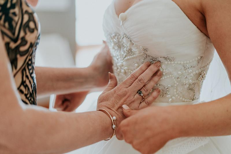 In this close-up shot, Agnew's mother uses her hands to feel the beading on the bodice of her daughter's wedding gown. (James Day Photography)