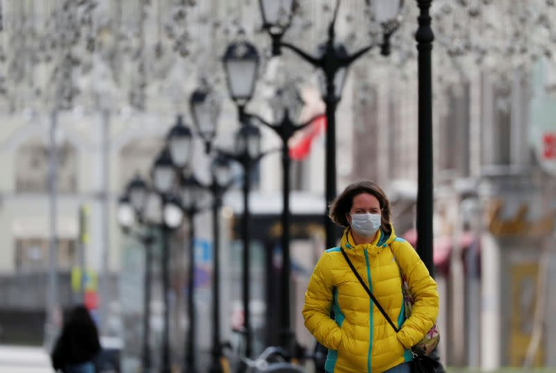 A woman wearing a protective face mask walks along the street in Moscow