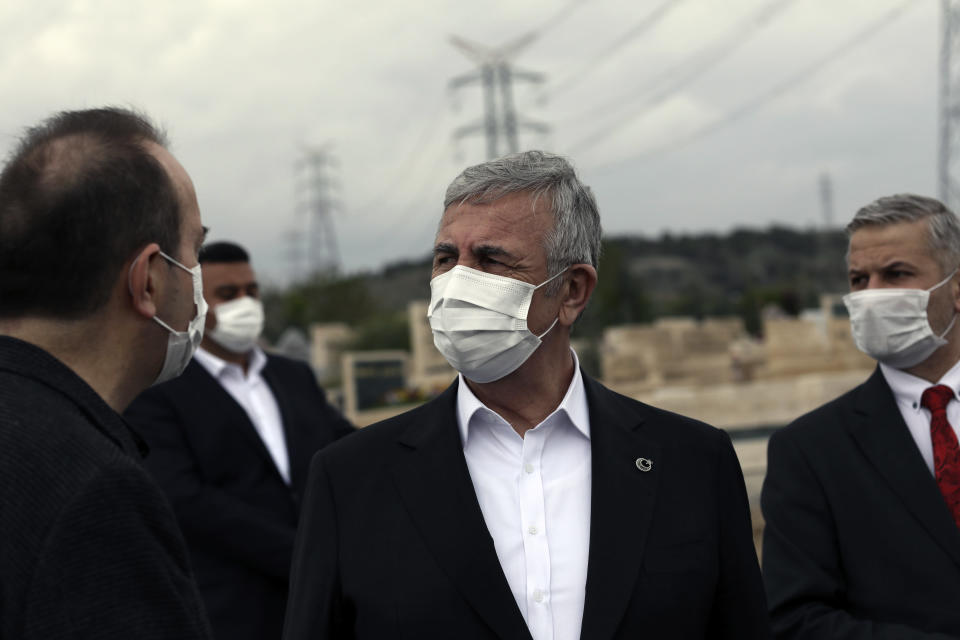 Ankara Mayor Mansur Yavas, center, and his advisors, wearing masks to help protect against the spread of coronavirus, speak in Ankara, Turkey, Thursday, May 6, 2021. Turkish security forces continue patrolling main streets and set up checkpoints at entry and exits points of cities to enforce Turkey's strictest COVID-19 lockdown to date.(AP Photo/Burhan Ozbilici)
