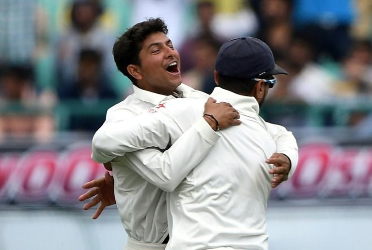 India's Kuldeep Yadav (L) celebrates the wicket of Australia's Peter Handscomb with teammate Murali Vijay during the fourth Test at The Himachal Pradesh Cricket Association Stadium in Dharamsala on March 25, 201