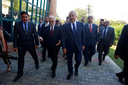 Turkish foreign minister Mevlut Cavusoglu walks with Iraqi Foreign Minister Ibrahim al-Jaafari in Baghdad, Iraq August 23, 2017. REUTERS/Khalid al Mousily