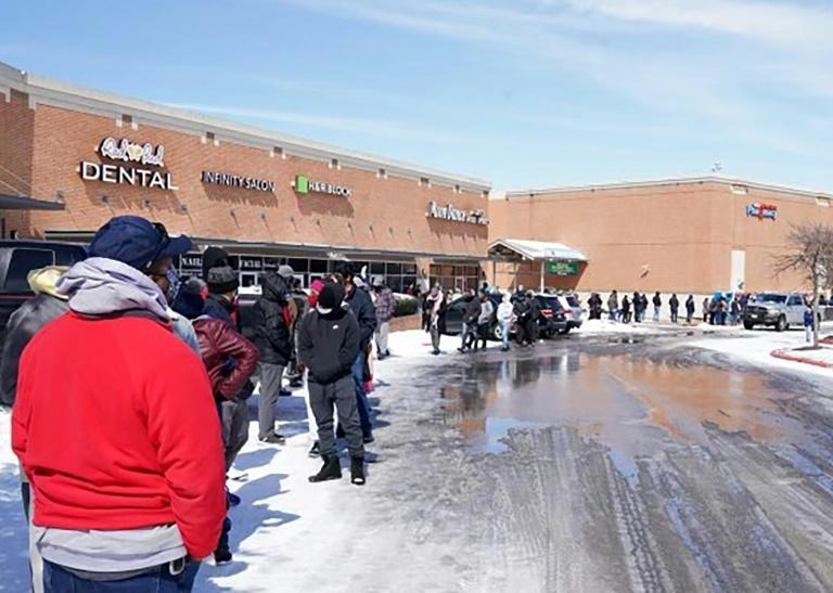 People wait in line at a mall to get inside an H-E-B supermarket in Round Rock, Texas, on February 16, 2021 as millions were left without power as a deadly winter storm gripped the southern and central United States
