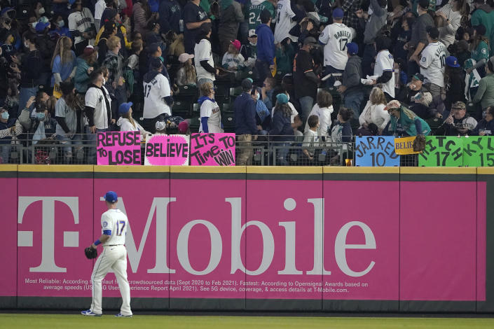 Seattle Mariners right fielder Mitch Haniger (17) watches as fans track a solo home run hit by Los Angeles Angels' Shohei Ohtani during the first inning of a baseball game, Sunday, Oct. 3, 2021, in Seattle. (AP Photo/Ted S. Warren)