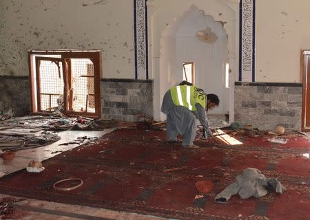 A rescue worker collects evidence after an explosion in a Shi'ite mosque in Shikarpur, located in Pakistan's Sindh province January 30, 2015. REUTERS/Amir Hussain