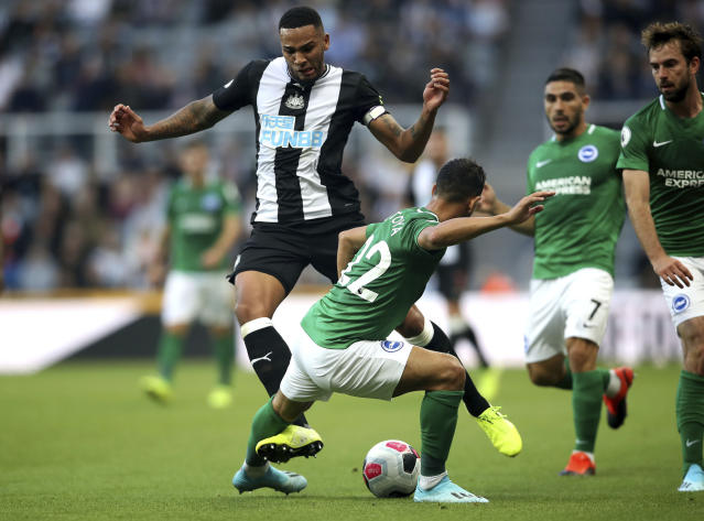 Newcastle United's Jamaal Lascelles, left, and Brighton and Hove Albion's Martin Montoya battle for the ball during the English Premier League match at St James' Park, Newcastle, England, Saturday Sept. 21, 2019. (Owen Humphreys/PA via AP)