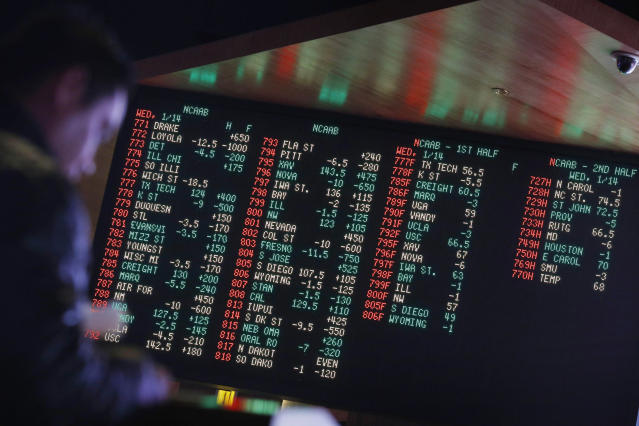 Sportsbooks have large boards that display point spreads for all games that day. (AP Photo/John Locher, File)