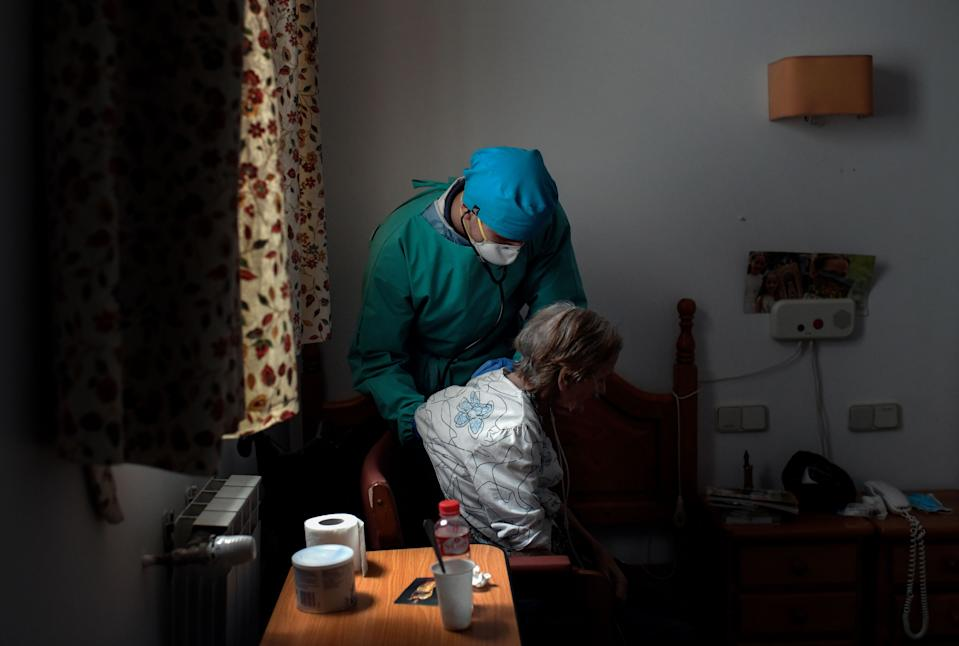 Venezuelan doctor Diego Padron examines an isolated resident at an elderly people nursing home in Madrid on April 24. Source: Getty Images