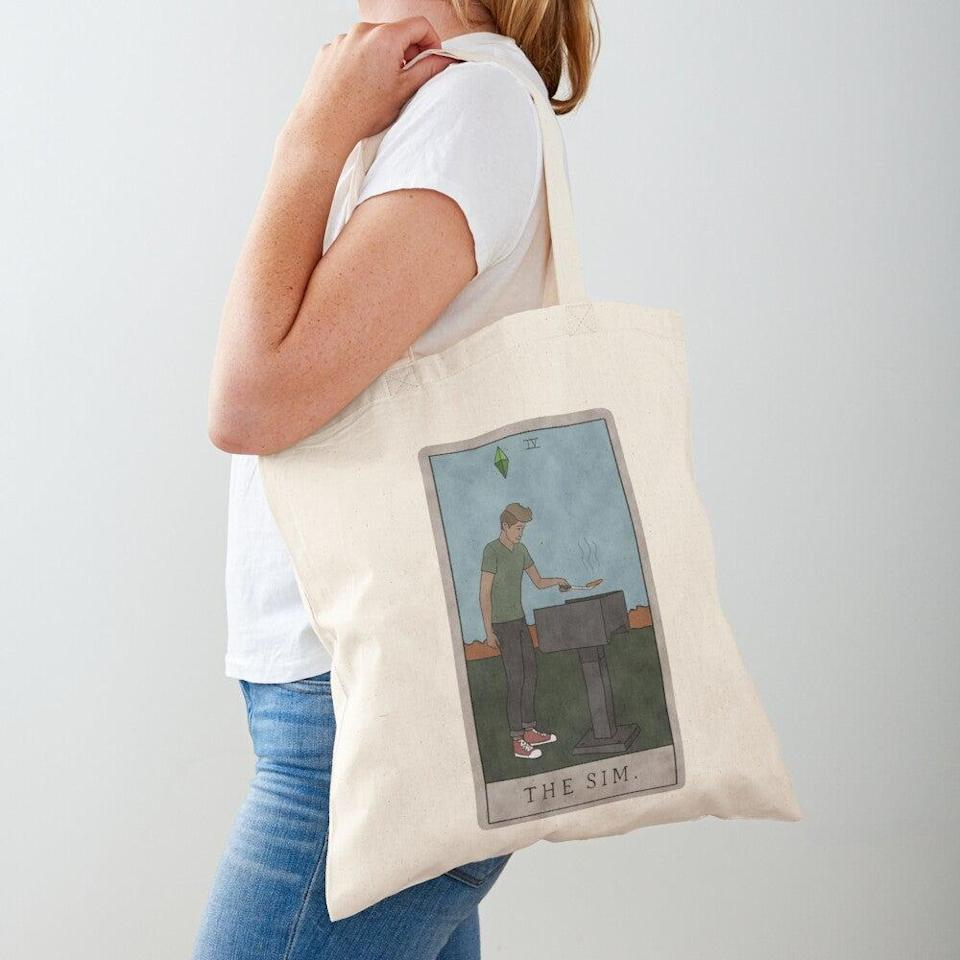 "<h2>The Sim Tote Bag</h2><br>If you want even more tarot x Sims crossovers, try this tote bag.<br><br><strong>Poppyheart</strong> The Sim Tote Bag, $, available at <a href=""https://go.skimresources.com/?id=30283X879131&url=https%3A%2F%2Fwww.redbubble.com%2Fi%2Ftote-bag%2FThe-Sim-by-Poppyheart%2F49053520.P1QBH"" rel=""nofollow noopener"" target=""_blank"" data-ylk=""slk:Redbubble"" class=""link rapid-noclick-resp"">Redbubble</a>"