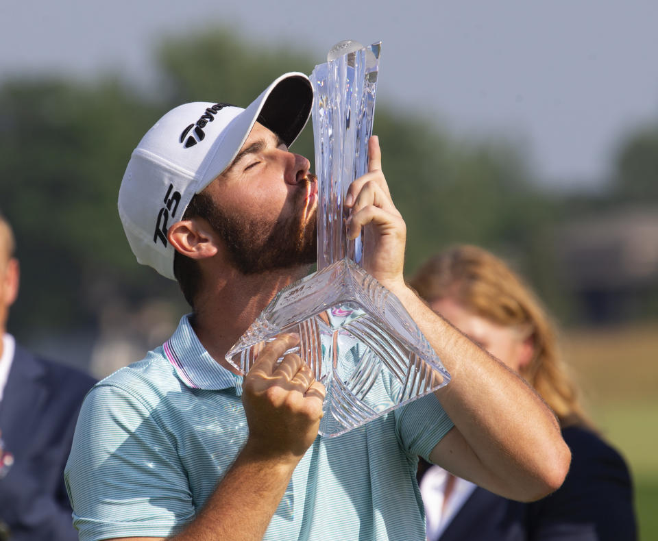 Matthew Wolff kisses the trophy after winning the 3M Open golf tournament Sunday, July 7, 2019, in Blaine, Minn. (AP Photo/Andy Clayton- King)