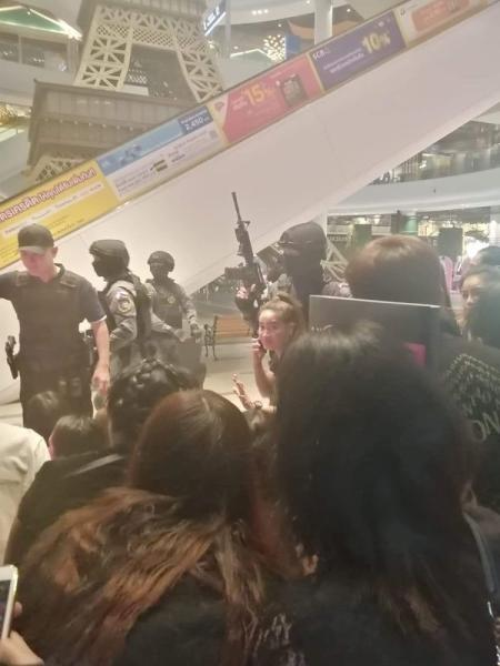 People are evacuated from a shopping mall by members of security forces after a shooting rampage in the city of Nakhon Ratchasima