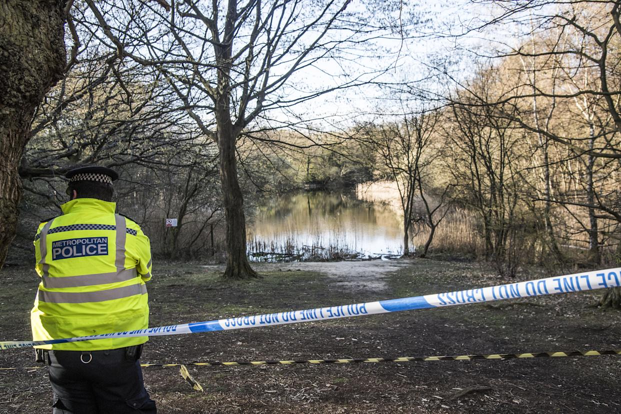 A Metropolitan Police officer at the scene at the Wake Valley pond in Epping Forest.