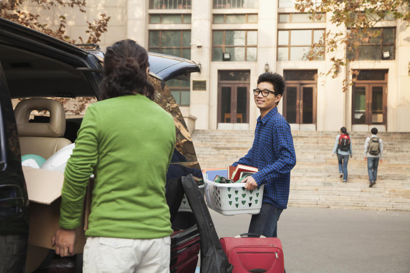 Young man moving into dormitory on college campus