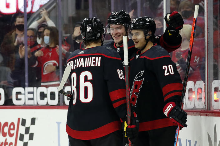 Carolina Hurricanes' Teuvo Teravainen (86) and Andrei Svechnikov (37) congratulate teammate Sebastian Aho (20) on his goal during the second period of an NHL hockey game against the Chicago Blackhawks in Raleigh, N.C., Monday, May 3, 2021. (AP Photo/Karl B DeBlaker)