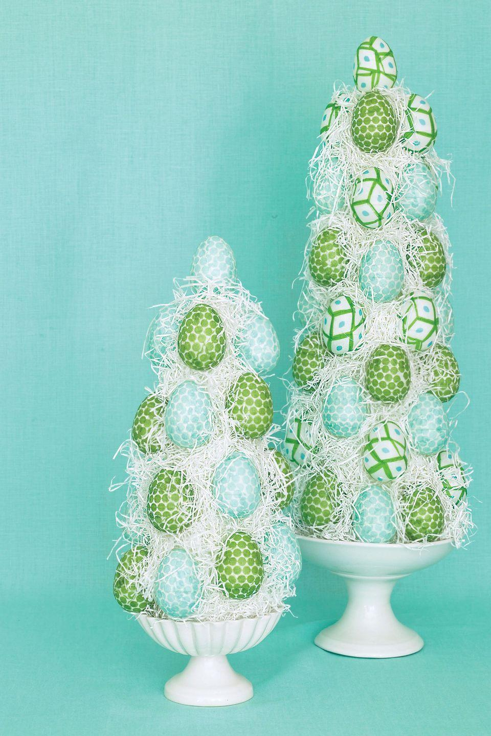"""<p>Feather your nest with topiaries made from paper napkin-covered plastic eggs glued onto Easter grass-covered Styrofoam cones.</p><p><strong><em><a href=""""https://www.womansday.com/home/crafts-projects/how-to/a5650/easter-craft-how-to-egg-topiary-116415/"""" rel=""""nofollow noopener"""" target=""""_blank"""" data-ylk=""""slk:Get the Easter Egg Topiaries tutorial."""" class=""""link rapid-noclick-resp"""">Get the Easter Egg Topiaries tutorial.</a></em></strong></p><p><strong><a class=""""link rapid-noclick-resp"""" href=""""https://www.amazon.com/Darice-01260P-1-Piece-Craftwork-9-85-Inch/dp/B00AF8I9E6/ref=dp_prsubs_1?pd_rd_i=B00AF8I9E6&psc=1&tag=syn-yahoo-20&ascsubtag=%5Bartid%7C10070.g.1751%5Bsrc%7Cyahoo-us"""" rel=""""nofollow noopener"""" target=""""_blank"""" data-ylk=""""slk:SHOP SYROFOAM CONES"""">SHOP SYROFOAM CONES</a></strong></p>"""