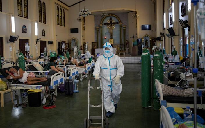 A health worker in full PPE walks out to get an oxygen tank for a Covid-19 patient, in the chapel of Quezon City General Hospital - that has been turned into a coronavirus ward amid rising infections - in Quezon City, Philippines - Eloisa Lopez/Reuters