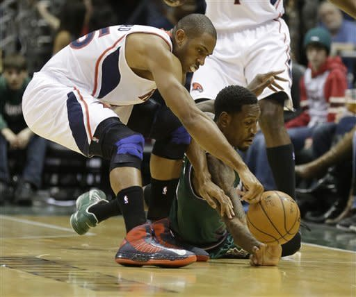 Atlanta Hawks' Al Horford, left, and Milwaukee Bucks' Larry Sanders, right, dive for the loose ball during the second half of an NBA basketball game, Saturday, Feb. 23, 2013, in Milwaukee. (AP Photo/Jeffrey Phelps)