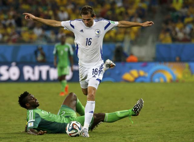Nigeria's Joseph Yobo falls to the ground as Bosnia's Senad Lulic goes for the ball during their 2014 World Cup Group F soccer match at the Pantanal arena in Cuiaba June 21, 2014. REUTERS/Eric Gaillard (BRAZIL - Tags: SOCCER SPORT WORLD CUP)