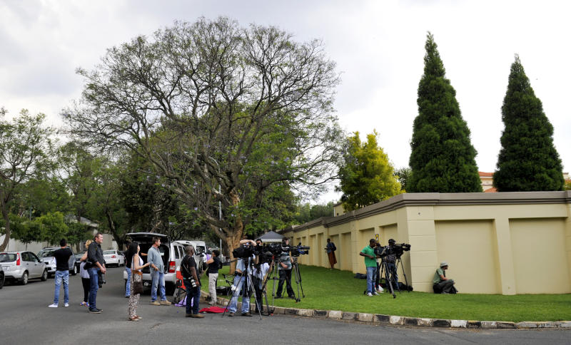 Members of the media train their cameras on former president Nelson Mandela's home, (unseen) in Johannesburg Friday, Dec 14, 2012. As the 94-year-old patriarch of South Africa's democracy entered his seventh day of hospitalization for a recurring lung infection, confusion grew as the government appeared to contradict itself over where he is being treated. (AP Photo)