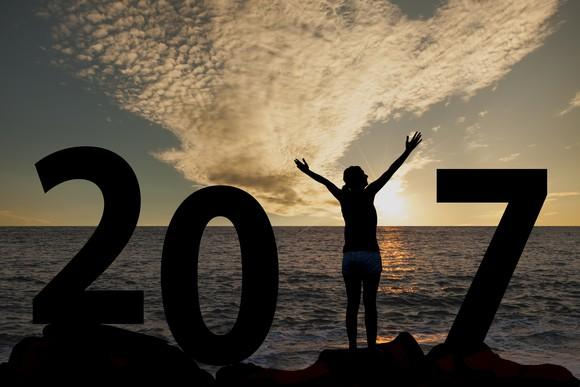 Image of a lady enjoying an ocean sunset with her arms held up signifying the number 1 in a large 2017 placed on a rocky shore.
