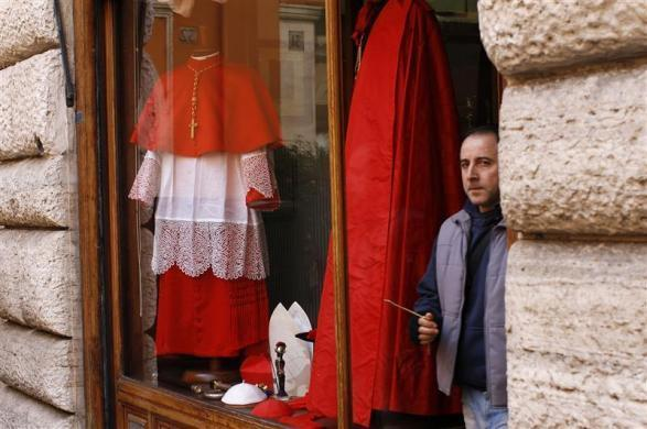 """A man walks past a shop window displaying cardinals' dresses in downtown Rome February 16, 2012. Pope Benedict will create 22 new red-hatted """"princes of the church"""" in a consistory ceremony at the Vatican."""