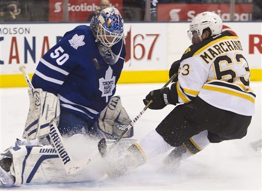 Toronto Maple Leafs goalie Jonas Gustavsson, left, makes a save on Boston Bruins forward Brad Marchand, right, during first period NHL hockey action in Toronto on Tuesday, March. 6, 2012. (AP Photo/The Canadian Press, Nathan Denette)