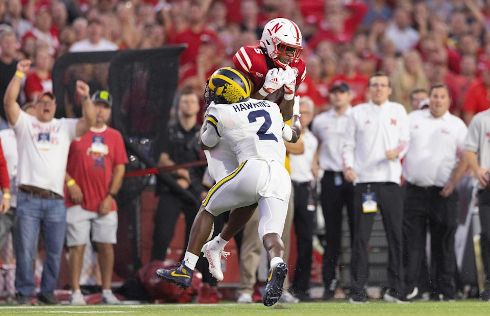 Nebraska's Omar Manning catches a pass as Michigan's Brad Hawkins defends during the first half on Saturday, Oct. 9, 2021, in Lincoln, Nebraska.
