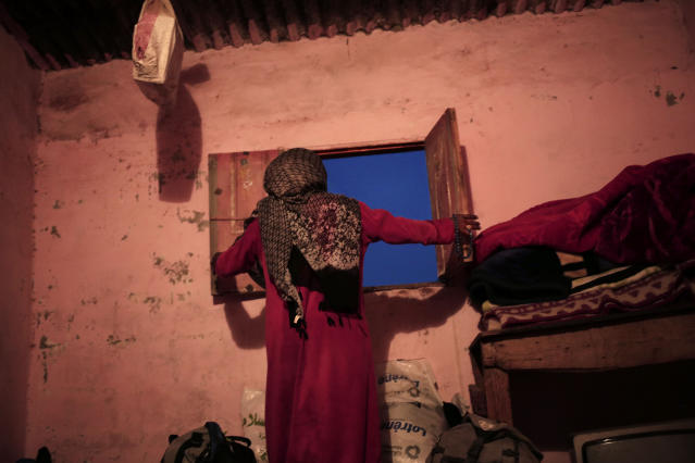 In this March 29, 2019 photo, Umm Yasser, closes the windows of her home, in Wadi Sahw, Abu Zenima, in South Sinai, Egypt. Umm Yasser is one of four women from the Hamada tribe who for the first time are working as tour guides. The tourists can only be women, and the tours can't go overnight. Each day before the sun sets, the group returns to the Hamada's home village in Wadi Sahu, a narrow desert valley. (AP Photo/Nariman El-Mofty)