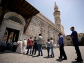 FILE PHOTO: People wear face masks as they wait in line to enter and attend the Friday prayers, after the government has eased the restrictions amid concerns over the coronavirus disease (COVID-19) outbreak, at Umayyad mosque in Damascus