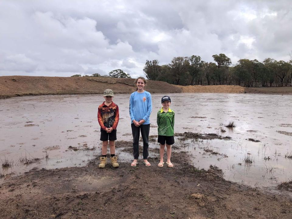 Ms Groth's children Brianna, 14, Jayden, 10, and Macklin, 8, are seen smiling as they stand in front of the quickly rising dam. Source: Lindsay Groth