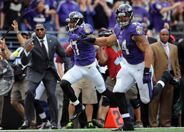 Baltimore Ravens wide receiver Tandon Doss, center, scores an 82-yard touchdown on a punt return as former Ravens linebacker Ray Lewis, back left, cheers him on, in the first half of an NFL football game against the Houston Texans, Sunday, Sept. 22, 2013, in Baltimore. (AP Photo/Gail Burton)