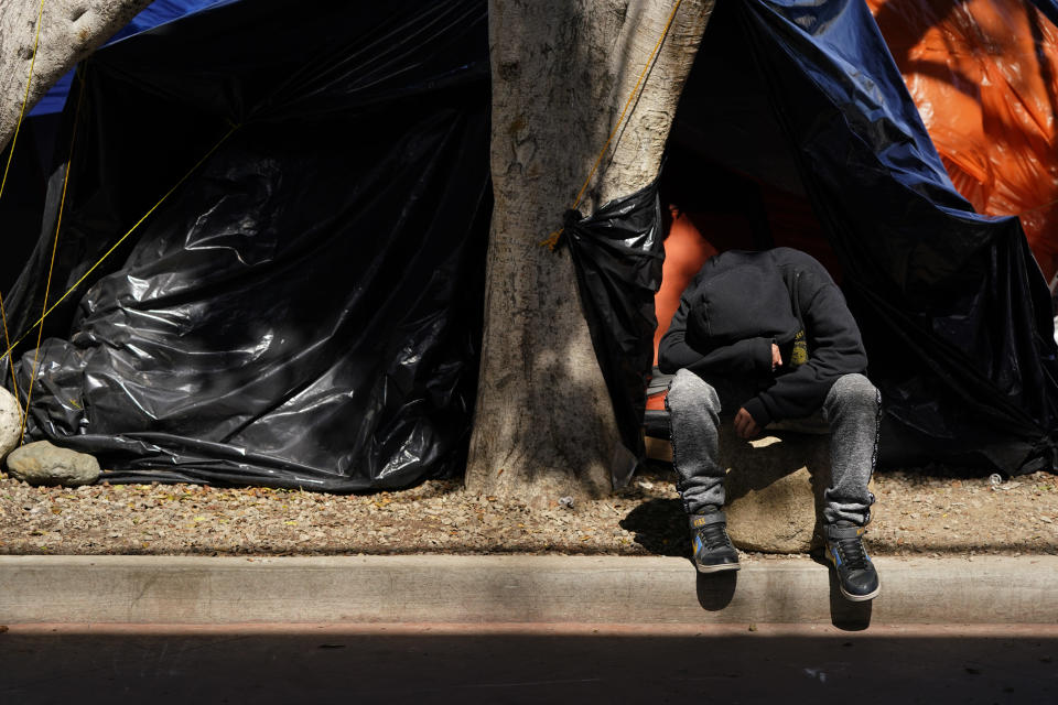 A boy sits in front of a tent housing several families at a makeshift camp of migrants at the border port of entry leading to the United States, Wednesday, March 17, 2021, in Tijuana, Mexico. The migrant camp shows how confusion has undercut the message from U.S. President Joe Biden that it's not the time to come to the United States. Badly misinformed, some 1,500 migrants who set up tents across the border from San Diego harbor false hope that Biden will open entry briefly and without notice. (AP Photo/Gregory Bull)
