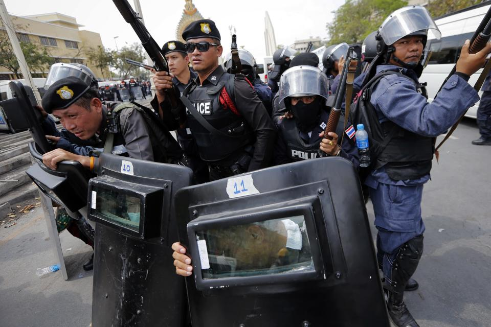 Police officers hold their weapons as they withdraw during clashes with anti-government protesters near the Government House in Bangkok February 18, 2014. A Thai police officer was killed and dozens of police and anti-government protesters were wounded in gun battles and clashes in Bangkok on Tuesday, officials and witnesses said. REUTERS/Damir Sagolj (THAILAND - Tags: POLITICS TPX IMAGES OF THE DAY CIVIL UNREST)