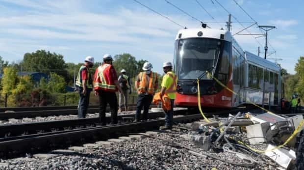 Ottawa's light rail network has been offline since last Sunday, when this train derailed near Tremblay station. An international firm has been selected to review any plans to resume service, but two members of the transit commission question the firm's independence. (Jean Delisle/CBC - image credit)