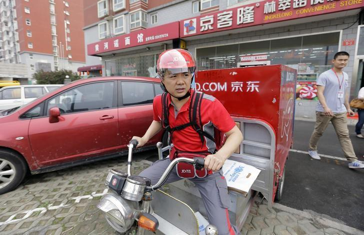 Liu, CEO and founder of China's e-commerce company JD.com, rides an electric tricycle as he leaves a delivery station in Beijing