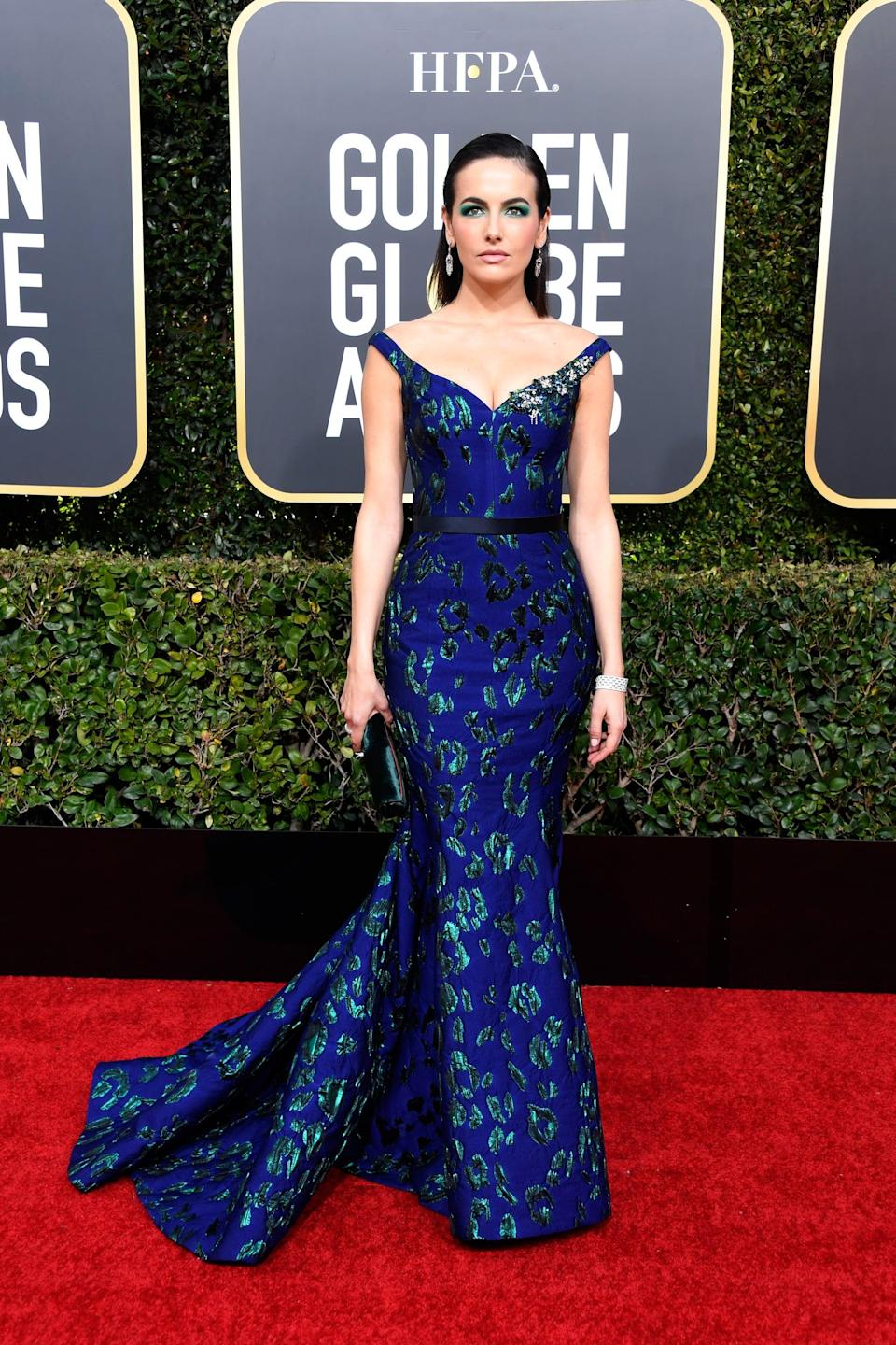 <p>Wearing a blue mermaid gown with Stuart Weitzman shoes and a Tyler Ellis clutch.</p>