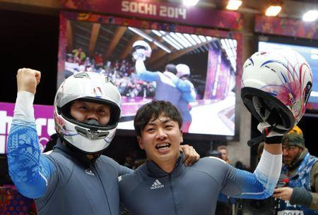 South Korea's pilot Won Yun-jong (front) and Seo Young-woo react after competing in the final run of the men's two-man bobsleigh competition at the 2014 Sochi Winter Olympics February 17, 2014. REUTERS/Arnd Wiegmann