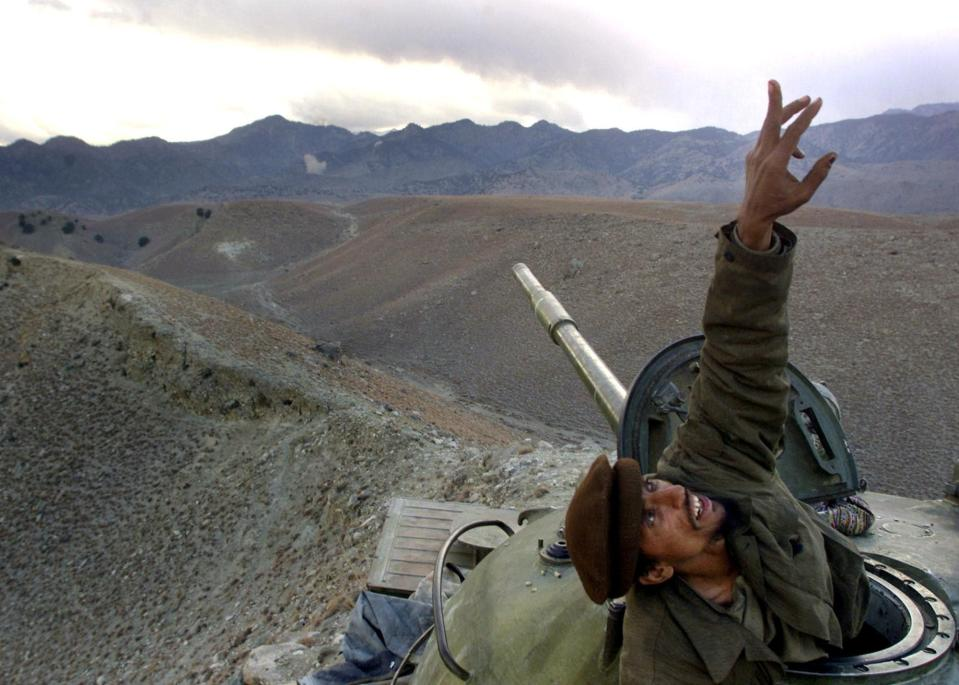 FILE - In this Dec. 10, 2001 file photo, an Afghan anti-Taliban fighter pops up from his tank to spot a U.S. warplane bombing al-Qaida fighters in the White Mountains of Tora Bora in Afghanistan. Anti-Taliban forces and U.S. warplanes continued to hit the Tora Bora mountains and the al-Qaida fighters occupying the area. (AP Photo/David Guttenfelder, File)