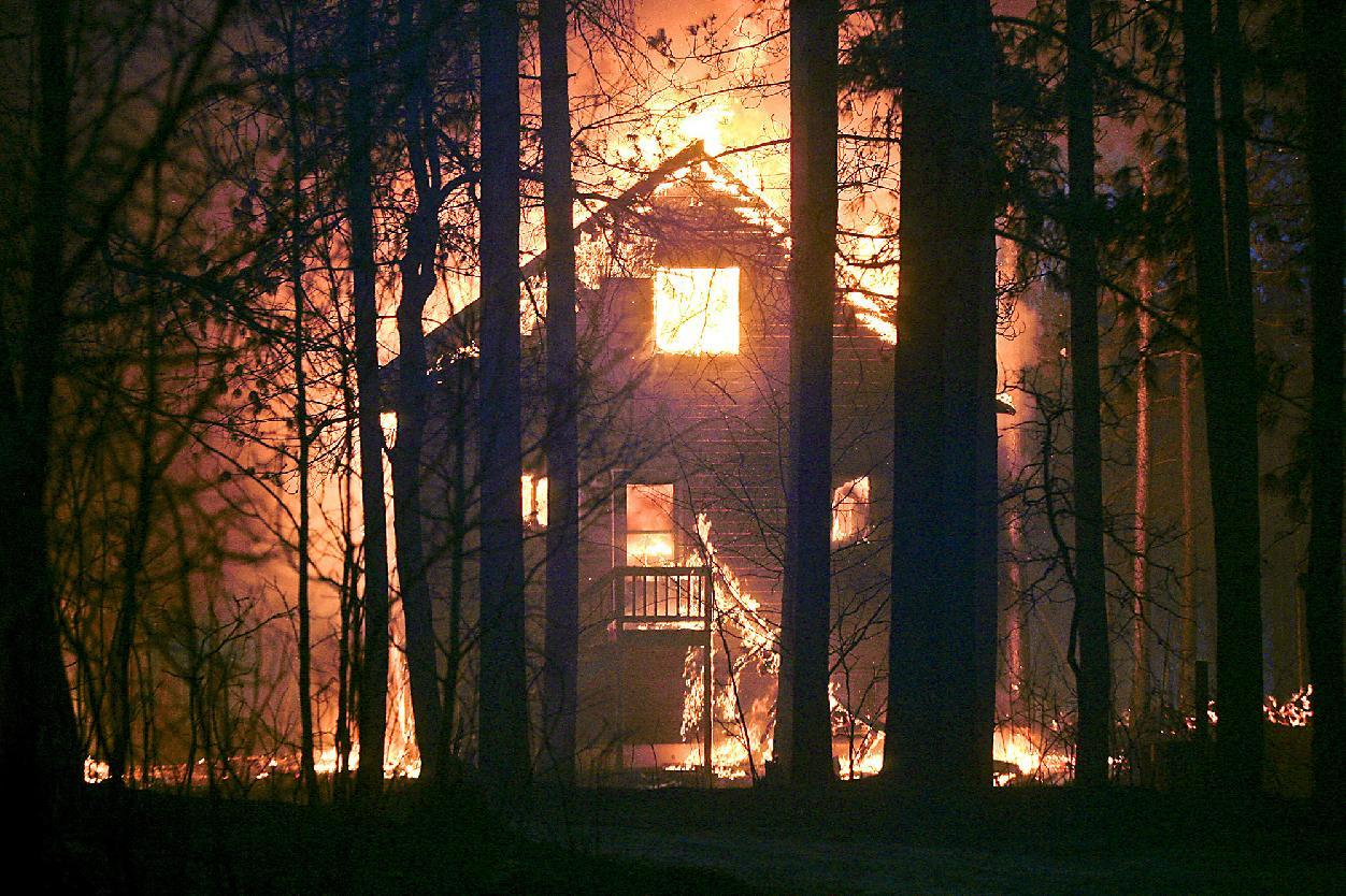 A home is on fire along Sutfin Road east of Comminsky Road in Highland Township, Wis., east of Solon Springs, Wis., late Tuesday, May 14, 2013. Crews from Wisconsin and Minnesota were trying to control a rapidly growing wildfire in northwestern Wisconsin that forced evacuations of the sparsely populated area. Several structures were destroyed in a mostly rural and wooded area east of Solon Springs as the forest fire grew to 9 square miles, the Wisconsin Department of Natural Resources said. No injuries had been reported. (AP Photo/The Duluth News-Tribune, Clint Austin)