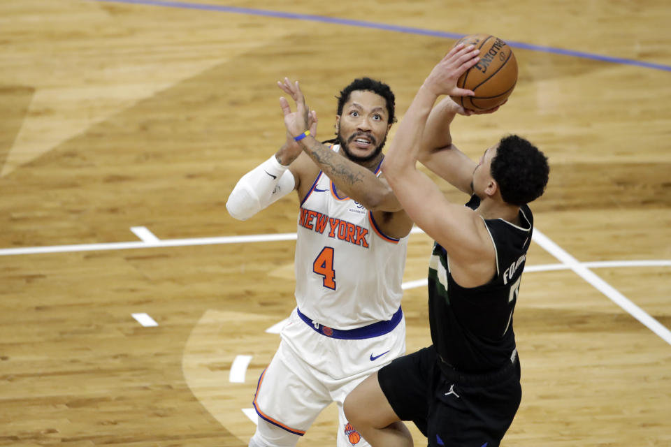 New York Knicks' Derrick Rose (4) defends against Milwaukee Bucks' Bryn Forbes during the second half of an NBA basketball game Saturday, March 27, 2021, in Milwaukee. (AP Photo/Aaron Gash)