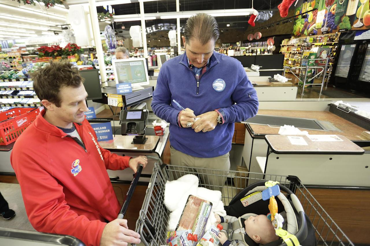 IMAGE DISTRIBUTED FOR FARMLAND - Kansas City Royals legend Mike Sweeney, right, signs an autograph at a local Price Chopper during the Farmland Fights Hunger event, Wednesday, Nov. 30, 2016, in Kansas City, Mo. For every Farmland product purchased through December 31st, twenty five cents will be donated to No Kid Hungry. (Colin E. Braley/AP Images for Farmland)