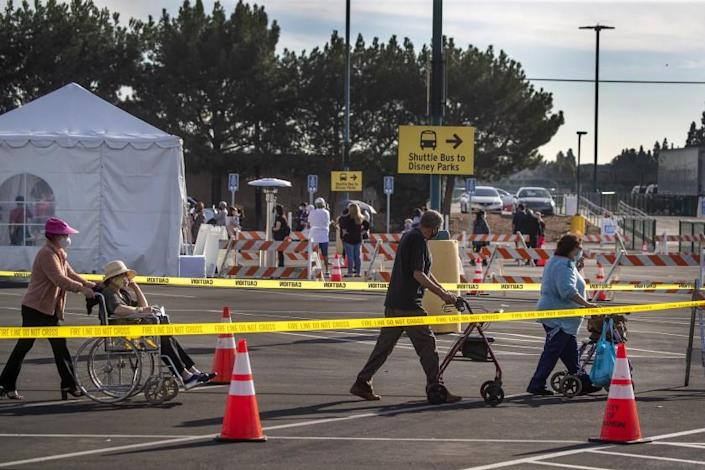 Anaheim, CA - January 13: Orange County active Phase 1A (critical and healthcare workers) residents exit large tents at Orange County's first large-scale vaccination site after receiving the Moderna COVID-19 vaccine in the Toy Story parking lot at the Disneyland Resort in Anaheim Wednesday, Jan. 13, 2021. Orange County supervisors and Orange County Health Care Agency Director Dr. Clayton Chau held a news conference discussing the county's first Super POD (point-of-dispensing) site for COVID-19 vaccine distribution. The vaccinations are at Tier 1A for people who have reservations on a website. The site is able to handle 7,000 immunizations per day. Their goal is to immunize everyone in Orange County who chooses to do so by July 4th. (Allen J. Schaben / Los Angeles Times)