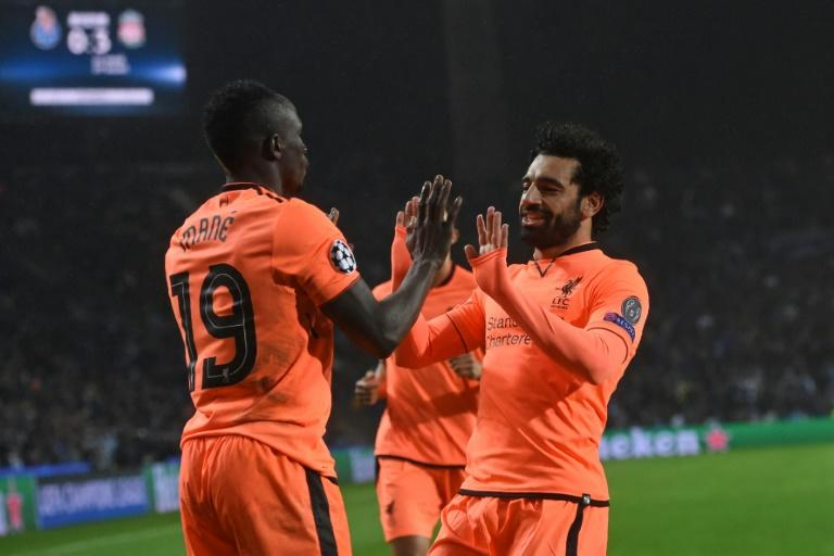Liverpool's Sadio Mane (L) celebrates with teammate Mohamed Salah after scoring a goal during their UEFA Champions League round of 16 first leg match against Porto, at the Dragao stadium in Porto, Portugal, on February 14, 2018