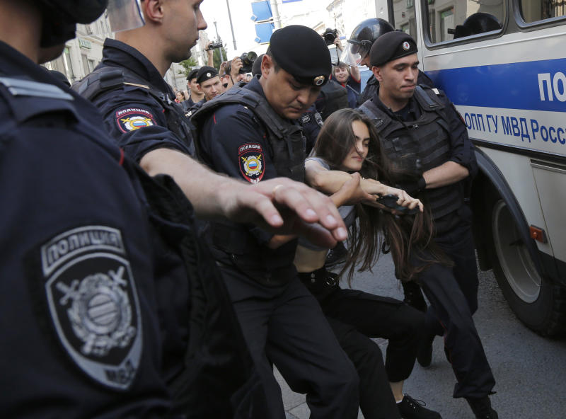 Police officers detain a woman prior to an unsanctioned rally in the center of Moscow, Russia, Saturday, July 27, 2019. OVD-Info, an organization that monitors political arrests, said about 50 people had been detained by 1:30 p.m. Saturday (1030 GMT), a half-hour before the protest against the exclusion of opposition figures from the ballot for city council elections was to start. (AP Photo/Alexander Zemlianichenko)