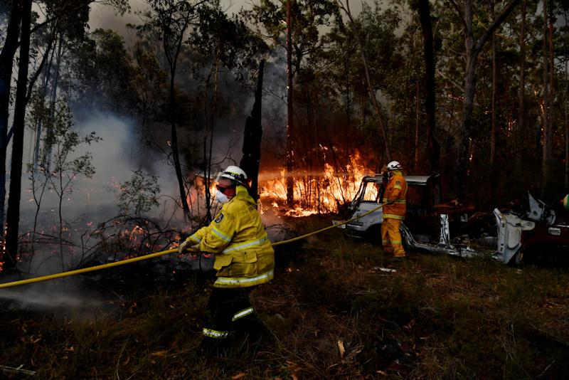 SYDNEY, AUSTRALIA - DECEMBER 31: Rural Fire Service (RFS) firefighters conduct property protection near the town of Sussex Inlet on December 31, 2019 in Sydney, Australia. There are a number of dangerous bushfires burning at emergency level across NSW as weather conditions deteriorate with temperatures expected to rise ahead of gusty southerly change. Princes Highway on the NSW South Coast has been closed with motorists told to avoid all non essential travel. Volunteer firefighter Sam McPaul was killed when his truck rolled over in a freak wind event near Jingellic near the NSW-Victorian border on Monday evening. (Photo by Sam Mooy/Getty Images)