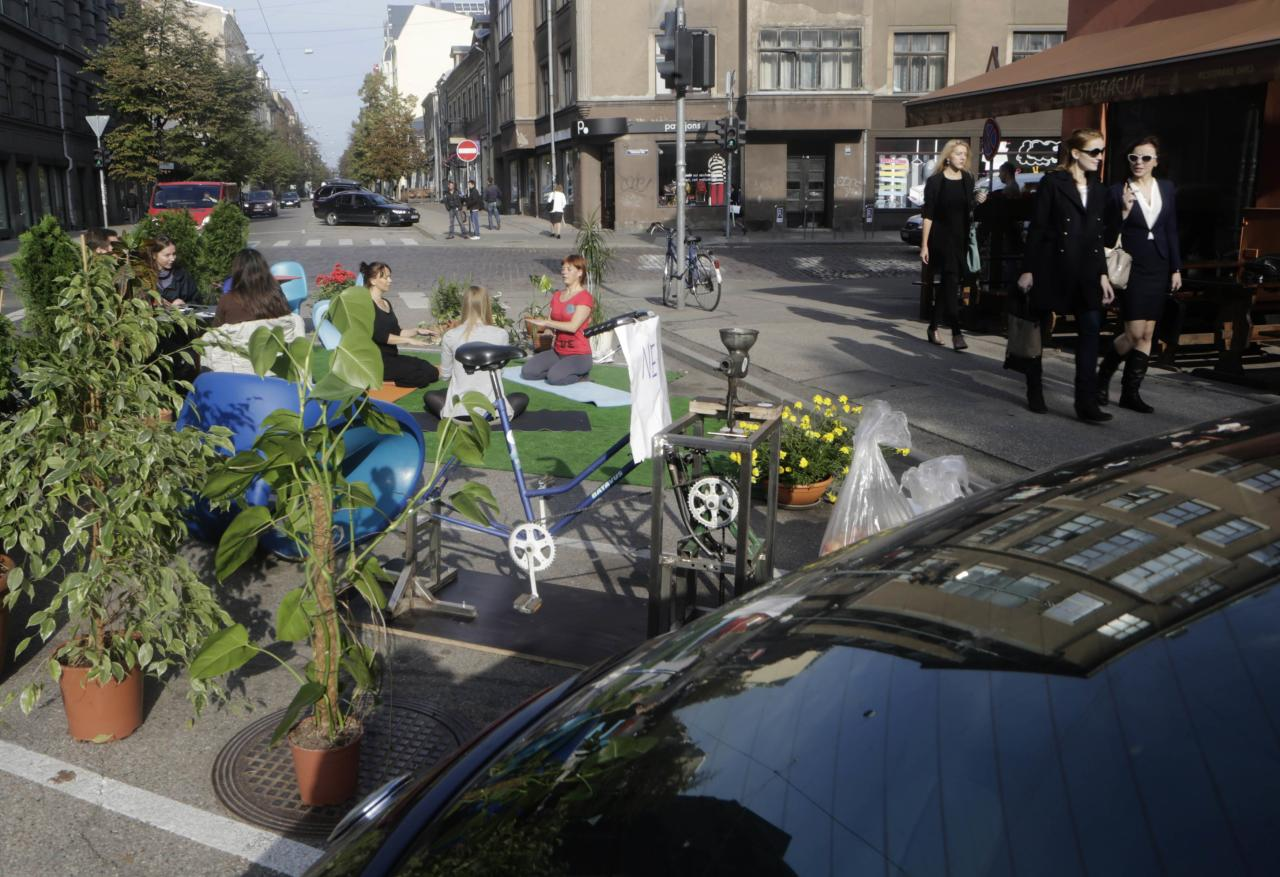 Pedestrians walk past people participating in a PARK(ing) Day event in Riga, September 20, 2013. The event aims to transform metered parking spaces into temporary public places to call attention to the need for more urban open spaces and discuss the creation and allocation of public spaces, according to organizers. REUTERS/Ints Kalnins (LATVIA - Tags: SOCIETY)