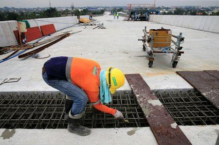 A construction worker stands over the newly dried concrete and secure linking steel bars of the 5.58 kilometre elevated highway in Caloocan City, metro Manila, Philippines on August 2, 2017.  REUTERS/Romeo Ranoco